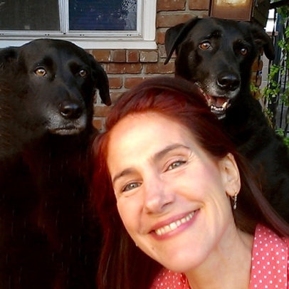 Photo of Daal with her two black lab mix dogs.