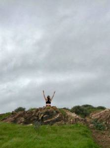 Photo of woman sitting atop a grassy hill, arms skyward