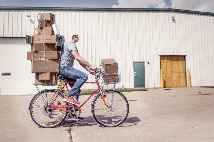 Bicycler with tiny head and many boxes