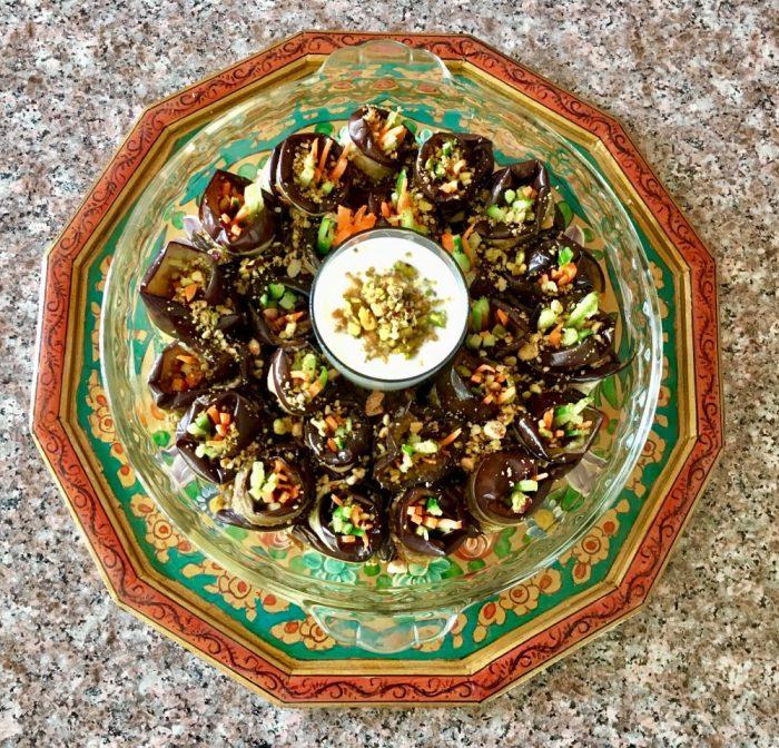 Platter of eggplant rollups with yogurt dip.