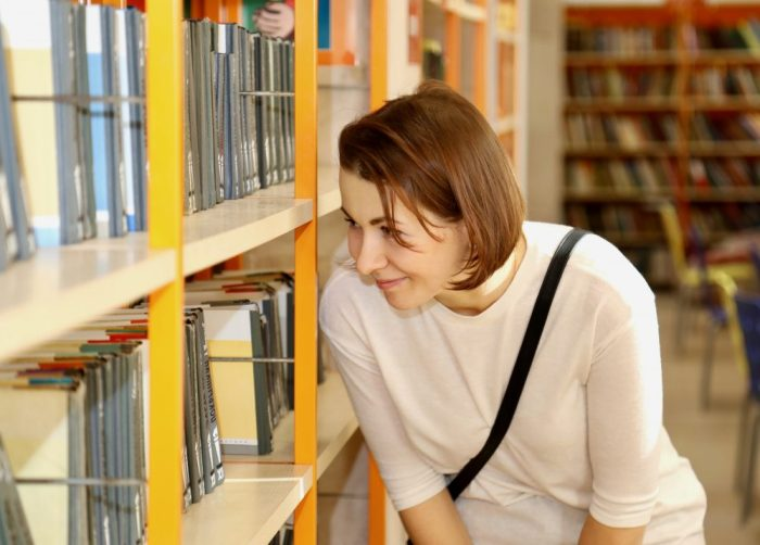 Photo of woman looking at books on shelves