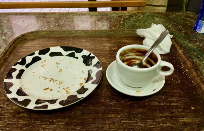 empty mug and plate of churros and hot chocolates