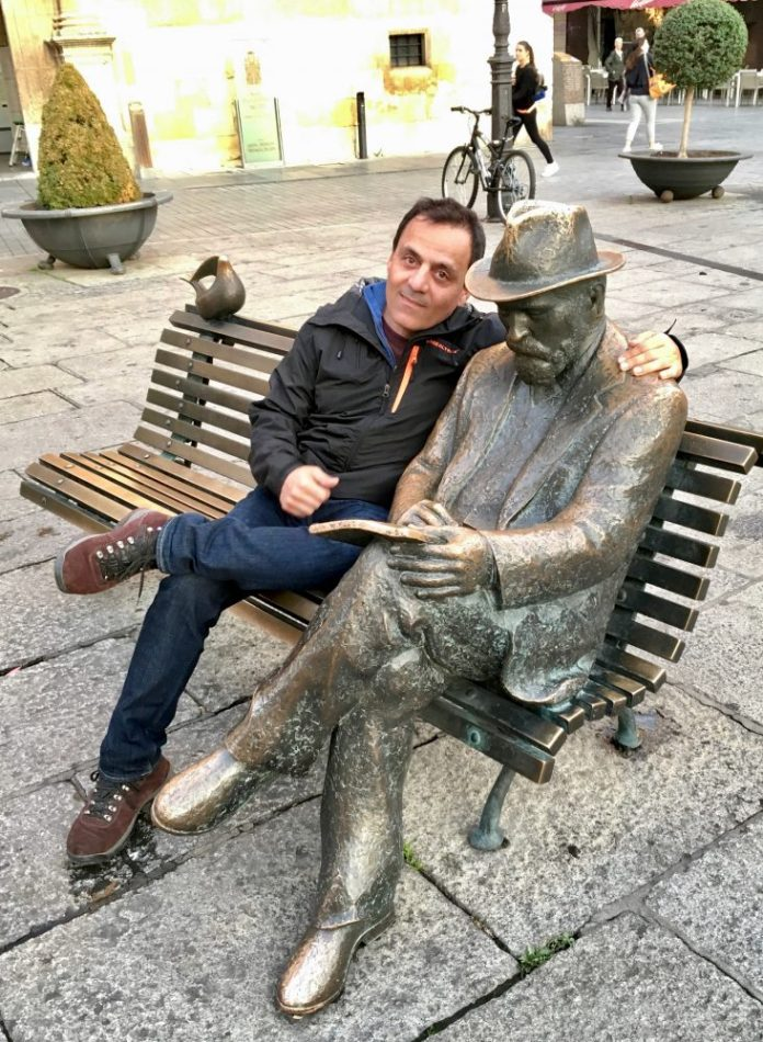 Photo of da-AL's husband sits with statue of Antoni Gaudí.