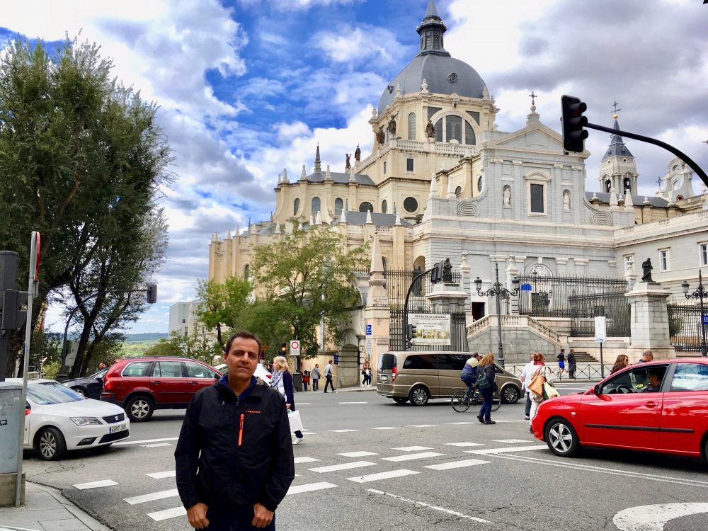 da-AL's husband stands before the palace of the king of Spain.