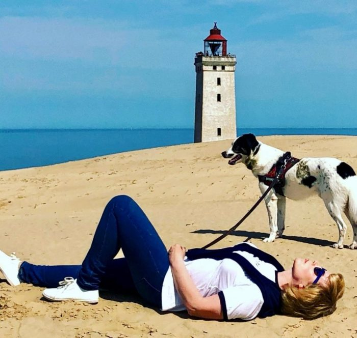 Valeska Réon lays on the sand, a watchtower in the background, with her dog.