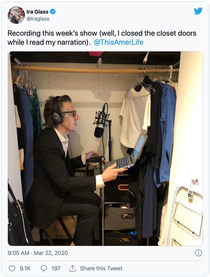 """Photo of Ira Glass recording an episode of his radio show, """"This American Life,"""" in his small closet."""
